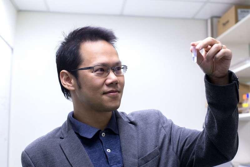 胡哲銘看著自己發明的冠狀病毒奈米疫苗,小小的容器裡充滿了 10000000000000 個薄殼中空奈米粒子。(圖/研之有物)