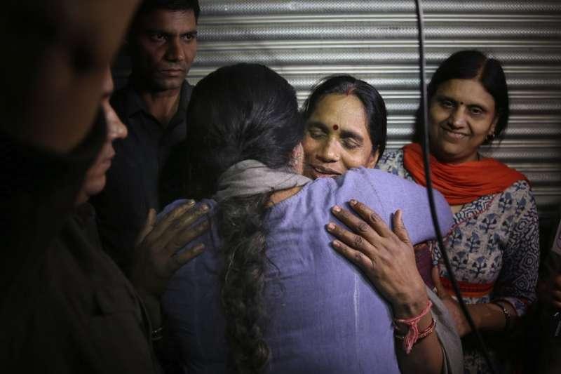 印度「公車輪姦案」4名兇手3月20日接受絞刑,受害女大學生的母親與支持者相擁。(AP)