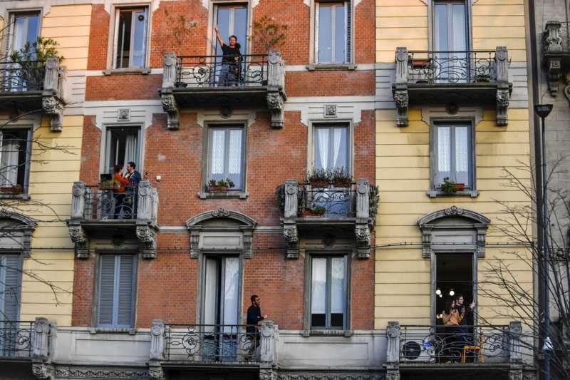 義大利疫情肆虐,民眾在陽台與窗戶邊為第一線防疫人員鼓掌致敬。(AP)