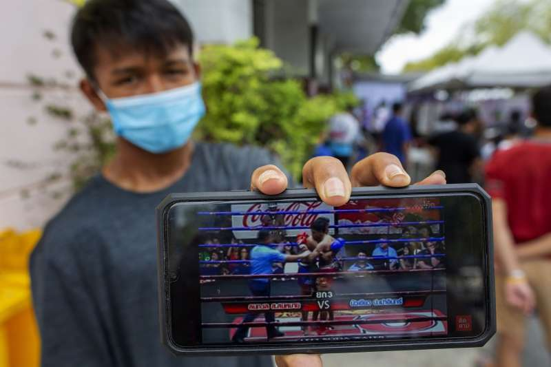 3月19日,一名泰拳選手在曼谷臨時篩檢站接受武漢肺炎篩檢,並展示紀錄他比賽的影片(美聯社)