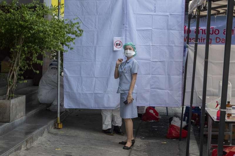 3月19日,泰國泰拳選手及相關人員在曼谷臨時篩檢站接受武漢肺炎篩檢,一名護士站在篩檢站外(美聯社)