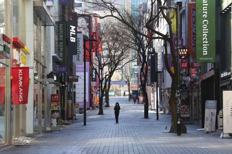 一位女性戴著口罩走過首爾的商店街。(美聯社)
