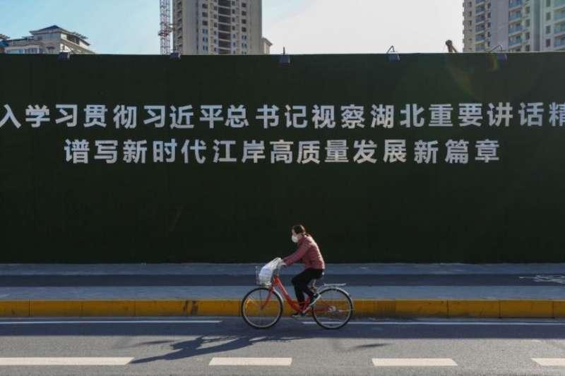 一名戴著口罩的婦女從武漢街頭一幅宣傳習近平湖北講話的大標語前騎車而過。(美國之音)