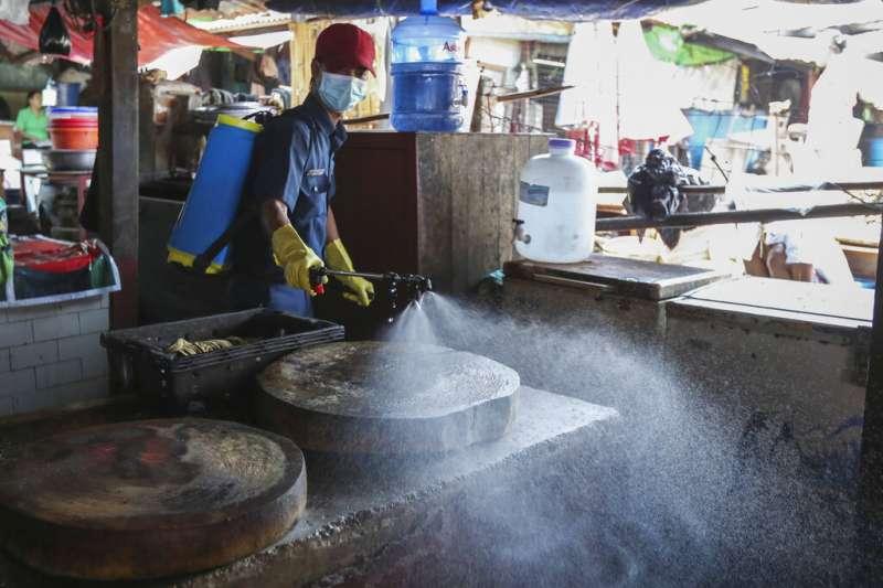 緬甸仰光一處市場正在進行消毒工作。(美聯社)