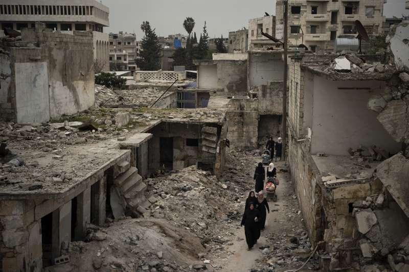 敘利亞伊德利卜省(Idlib),居民走在空襲殘垣間。(美聯社)