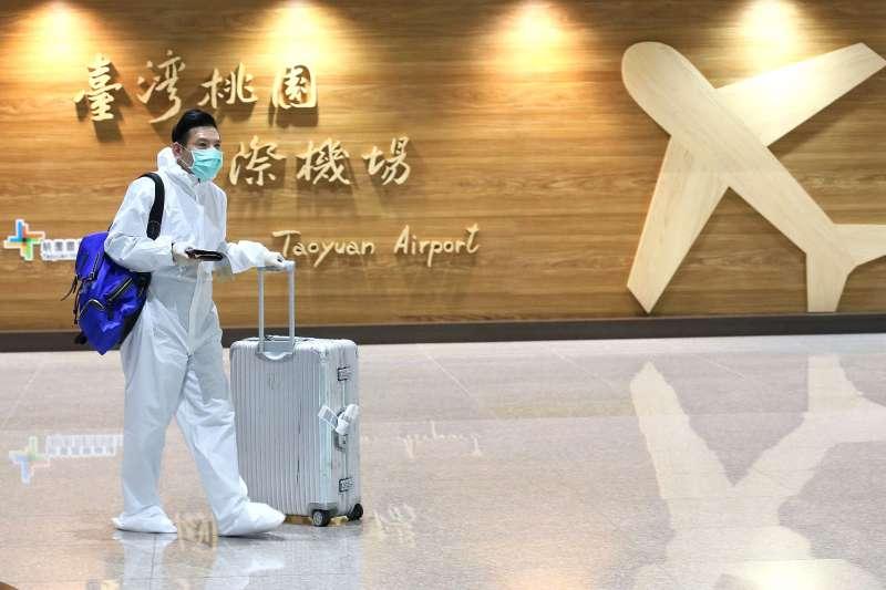20200326-因武漢肺炎疫情管控出入境,桃園機場單日出入境人數已跌破萬人,圖為一位穿著全身防護衣入境的旅客 .(柯承惠攝)