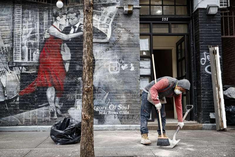 美國紐約街頭,一名戴著口罩的工人正在清掃街道。(美聯社)