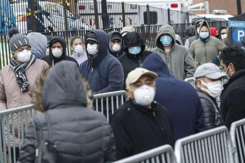 美國艾姆赫斯特醫院外頭,多位戴著口罩的民眾排隊等待接受武漢肺炎的篩檢(美聯社)