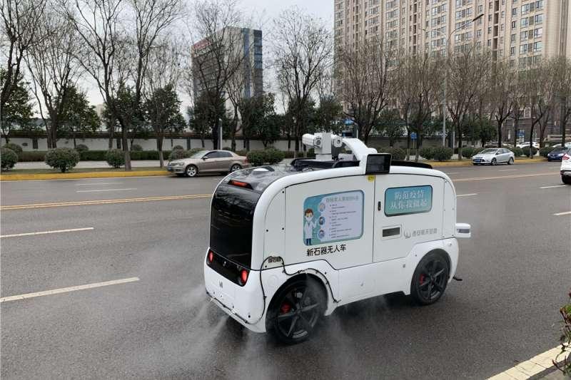 由交叉資訊核心技術研究院推出的5個無人防疫車正在路上執行消殺工作。(新華社)