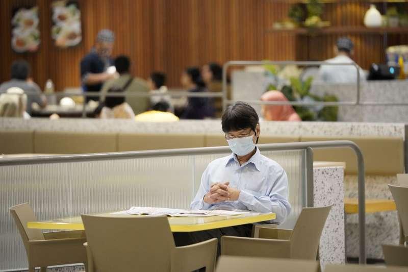 馬來西亞的武漢肺炎疫情延燒,吉隆坡一處美食廣場內,一名戴著口罩的男子正在讀報(美聯社)