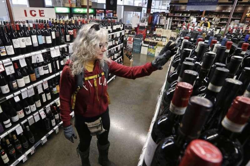 在英國與美國許多地方,酒類專賣店被視為封城狀態下的例外,得以正常經營。圖為美國西雅圖一間酒類專賣店。(AP)