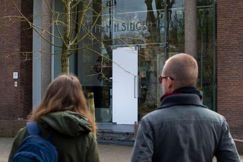 荷蘭辛格拉倫博物館30日凌晨遭闖入,梵谷名畫遭竊,兩名路人看著遭竊賊破壞的博物館玻璃門(美聯社)