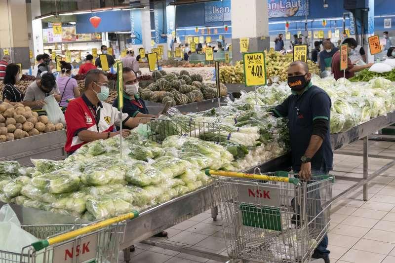 馬來西亞為防疫限制人民活動,但出門購物的男性一家之主卻不識蔬果,連超市都看不下去。(AP)
