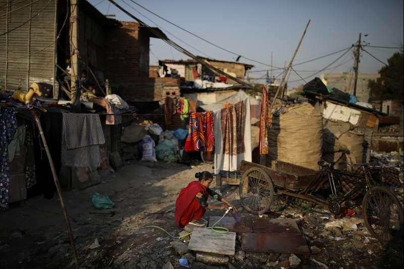 武漢肺炎疫情在全球蔓延,窮人受到嚴重衝擊。圖為印度新德里貧民窟一名婦女正在裝水(美聯社)