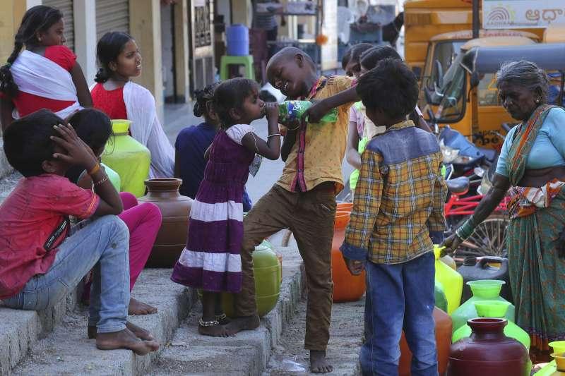 武漢肺炎疫情在全球蔓延,窮人受到嚴重衝擊。圖為印度海德拉巴貧困社區的人們正等著裝水(美聯社)