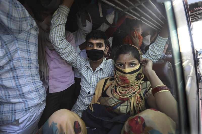 武漢肺炎疫情在全球蔓延,窮人受到嚴重衝擊。印度的日薪工人為了維生,只能搭著擁擠的公車去工作(美聯社)