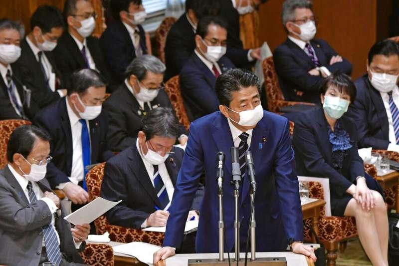 日本首相安倍晉三與大部分的國會議員終於戴上口罩。(美聯社)