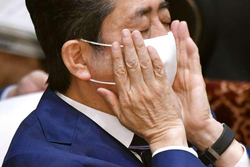 日本首相安倍晉三終於戴上口罩在國會備詢。(美聯社)
