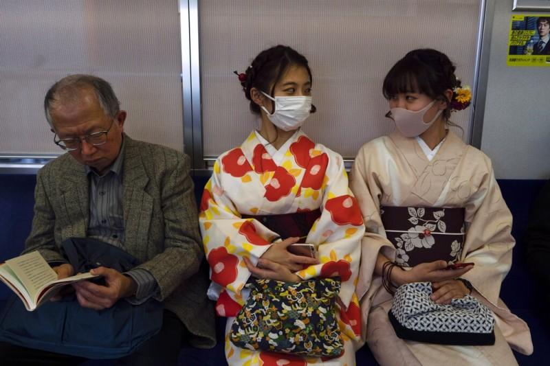 京都電車上的兩位日本女性戴著口罩搭車。(美聯社)