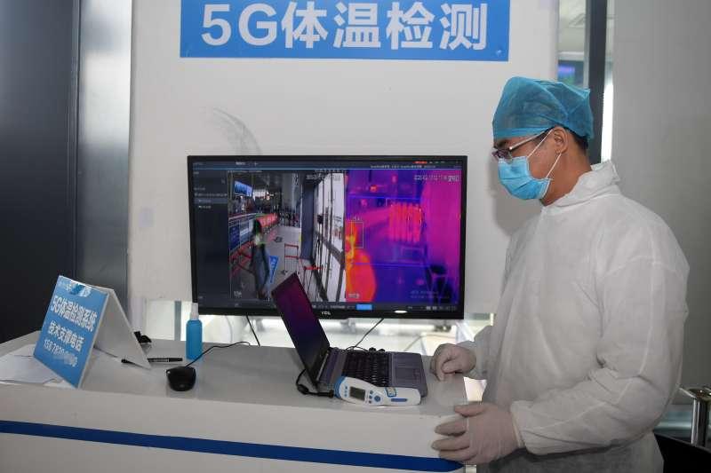 在中國廣西南寧東站,工作人員運用5G體溫檢測系統對進站旅客進行測溫(新華社)