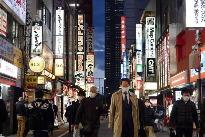 日本受新冠肺炎(武漢肺炎)衝擊,東京3月27日上街民眾多半戴著口罩。(AP)