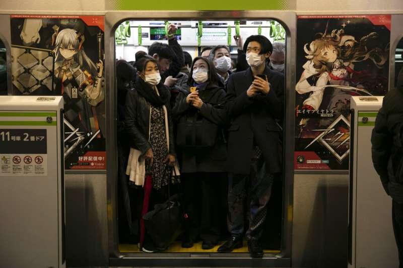 日本受新冠肺炎(武漢肺炎)衝擊,東京通勤族戴著口罩搭電車。(AP)