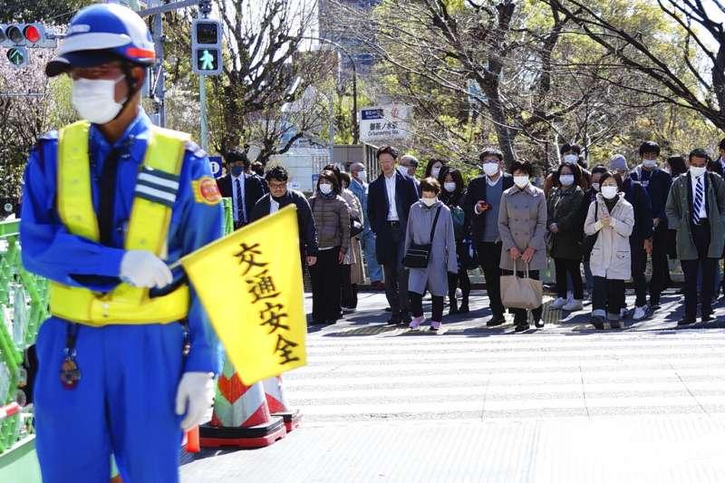 日本受新冠肺炎(武漢肺炎)衝擊,政府呼籲在家上班、盡量別外出。4月2日,仍有許多上班族戴口罩出門工作。(AP)
