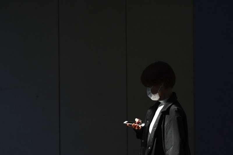 東京地下道一位戴著口罩的市民。(美聯社)