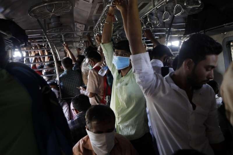 3月20日,印度孟買,通勤人潮將車廂擠得水洩不通,一些乘客戴著口罩(美聯社)