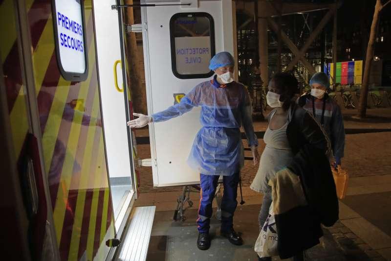 法國民防安全局人員護送一名疑似感染武漢肺炎的巴黎孕婦上救護車(美聯社)