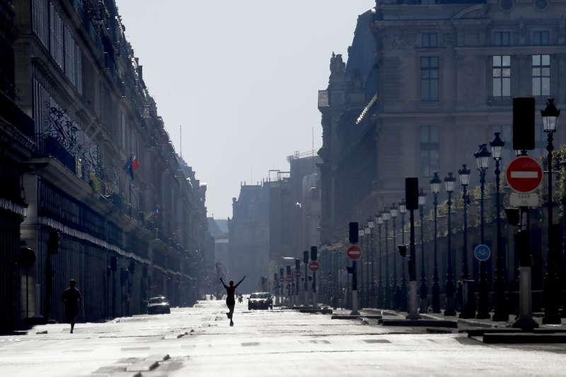 從3月17日起,法國全境封鎖。4月5日,巴黎知名商業街「里沃利街」人煙稀少,有一人慢跑,一名女子伸展身體(美聯社)
