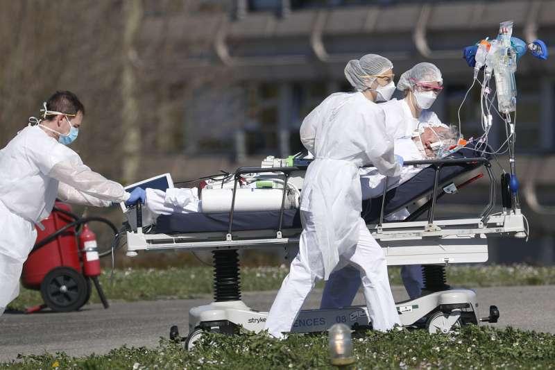 3月23日,法國東北部城市米盧斯醫護人員正將一名武漢肺炎病患撤離至他處(美聯社)