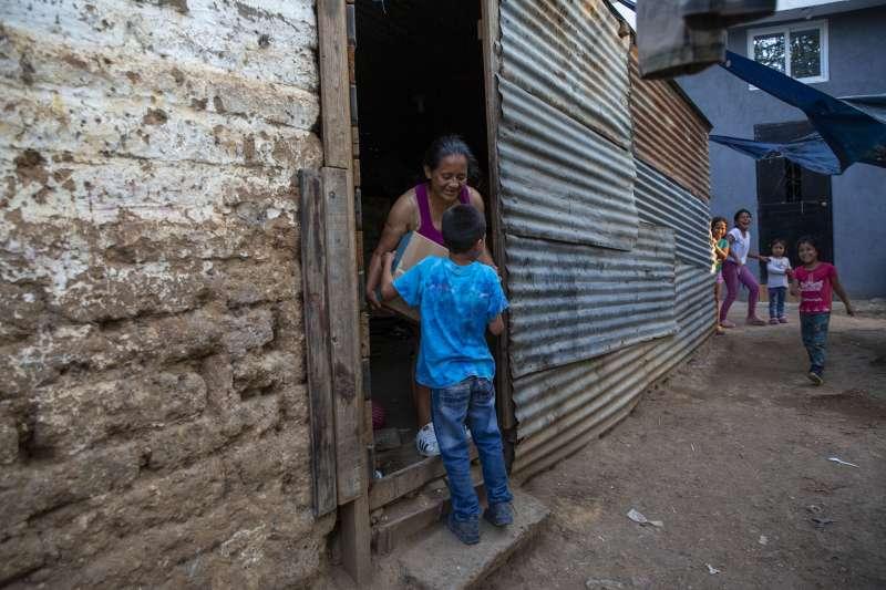 武漢肺炎疫情衝擊全球,全球窮人大受衝擊。圖為瓜地馬拉首都一名婦女收到政府在防疫期間發放的物資(美聯社)