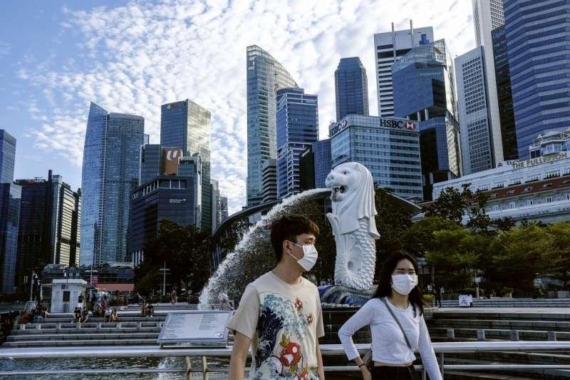 3月14日,戴著口罩的路人行經新加坡魚尾獅公園(美聯社)
