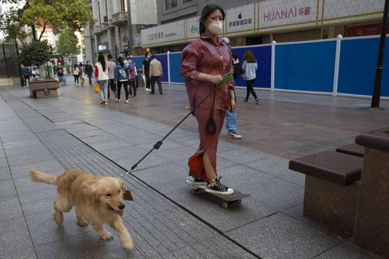 中國武漢爆發新冠肺炎期間,居民戴口罩出門遛狗。(資料照,AP)