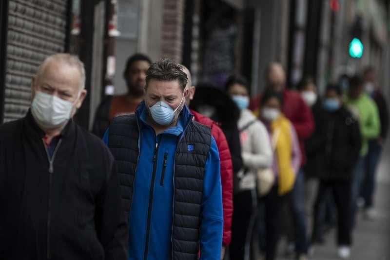 西班牙民眾戴著口罩排隊入商店。武漢肺炎疫情衝擊經濟,西班牙政府擬推無條件基本收入(UBI)。(AP)