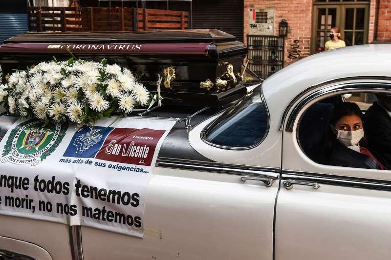 有哥倫比亞的葬儀公司職員,駕著寫上「人終有一死,但我們要試著別殺死對方」標語的車,在安蒂奧基亞省內宣傳抗疫。(圖片來源:JOAQUIN SARMIENTO/AFP|cup提供)
