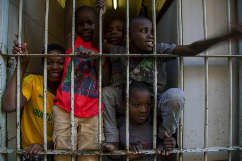 專家警告新冠肺炎(武漢肺炎)將對非洲造成「生存威脅」。南非一間公寓的孩子們向外看去。(AP)