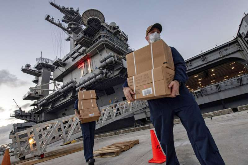 停靠關島的「羅斯福號」航母水兵正在搬運補給品與新冠病毒篩驗試劑。(美聯社)