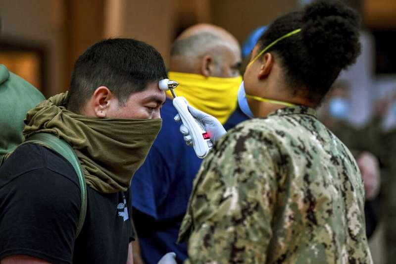 美軍的醫療人員正在為「羅斯福號」水兵進行病毒篩檢。值得注意的是,水兵們並沒有配戴口罩,而是用衣物克難代替。(美聯社)