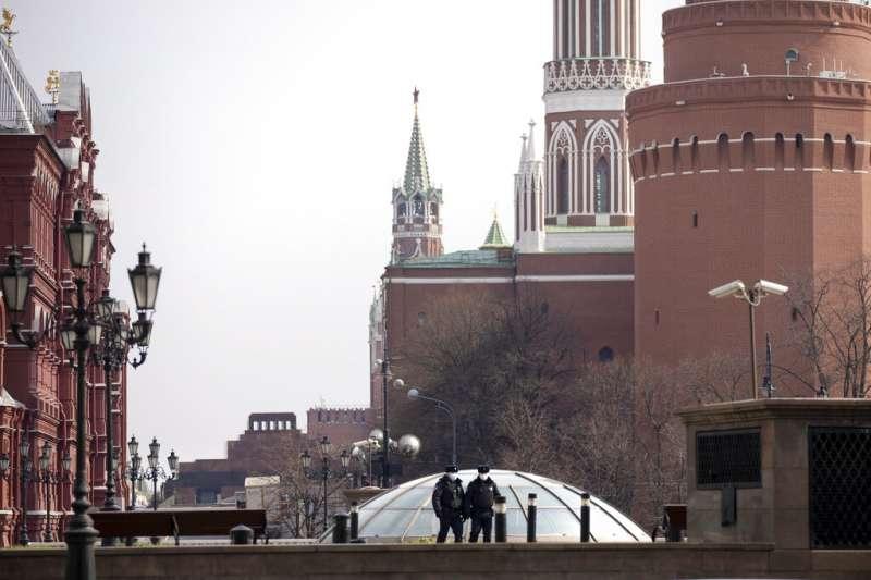 莫斯科封城後,許多昔日熱鬧的景點幾乎看不到外出的遊人,紅場上只有兩位戴著口罩的警察。(美聯社)
