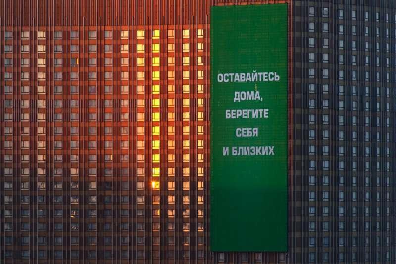 莫斯科一棟大樓的外牆上用俄文寫著:待在家裡,照顧好你自己跟你愛的人。(美聯社)
