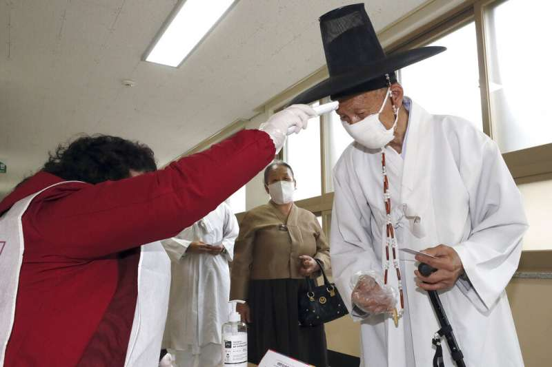 南韓4月15日舉行國會大選,由於新冠肺炎疫情仍未解除,民眾與投票所人員都嚴陣以待、手套口罩戴好戴滿。(美聯社)