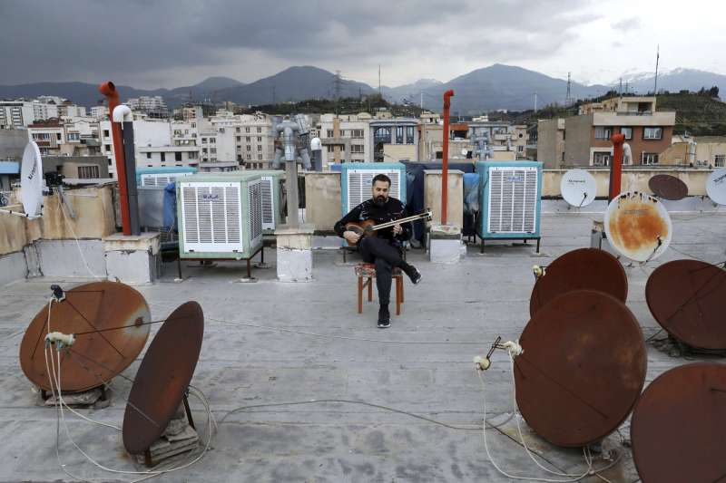 法拉杰涅吉德在屋頂演奏樂器「塔爾」(美聯社)