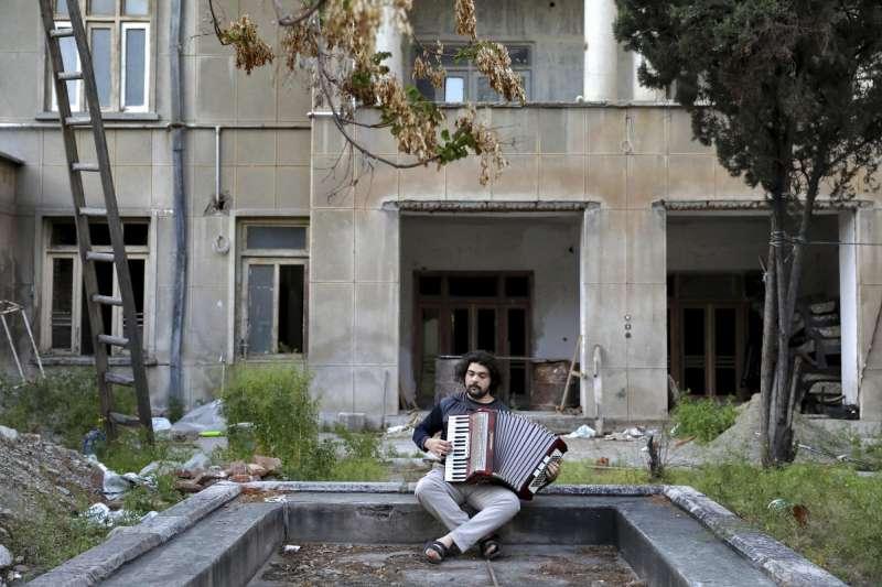 26歲的手風琴演奏家賈法利(Kaveh Ghafari)在自家院子演奏(美聯社)