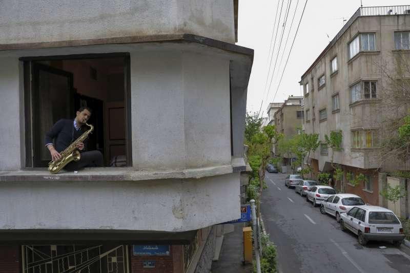 伊朗國家樂團的成員、23歲的馬勒克里坐在德黑蘭住處的窗邊演奏薩克斯風(美聯社)