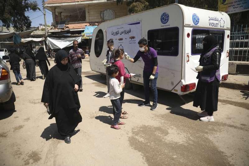 武漢肺炎:非政府援助機構人員在敘利亞伊德利卜省為民眾量體溫(AP)