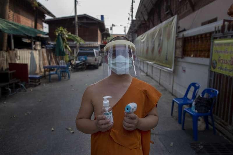 4月15日,泰國曼谷Molilokayaram佛寺的一名僧侶戴著面罩與口罩,拿著手部消毒劑與額溫槍站在寺廟開設的學院入口(美聯社)