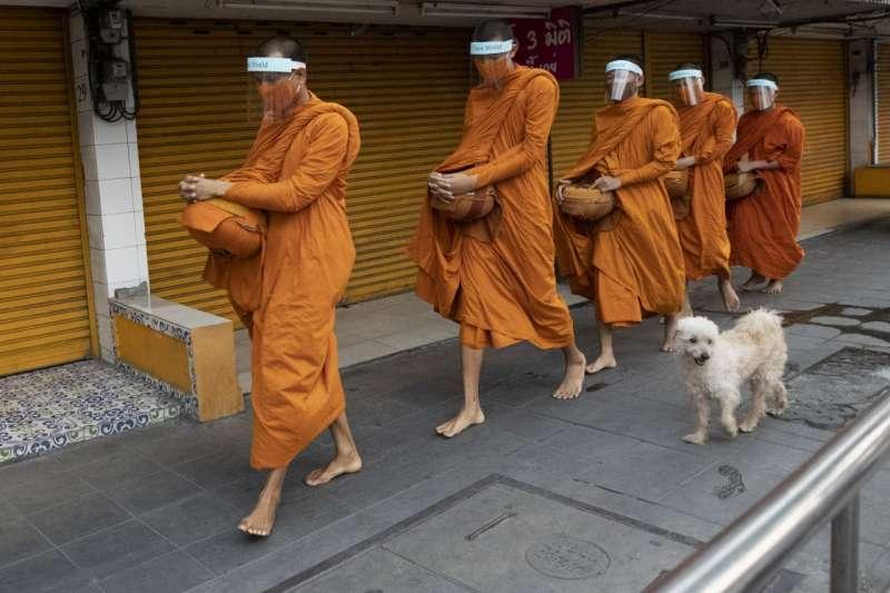 泰國曼谷的僧侶帶著面罩與口罩上街化緣(美聯社)