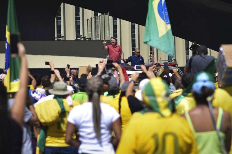 巴西總統博索納羅19日加入在首都巴西利亞軍方總部外示威的民眾,一同抗議州長頒布的居家令。(美聯社)